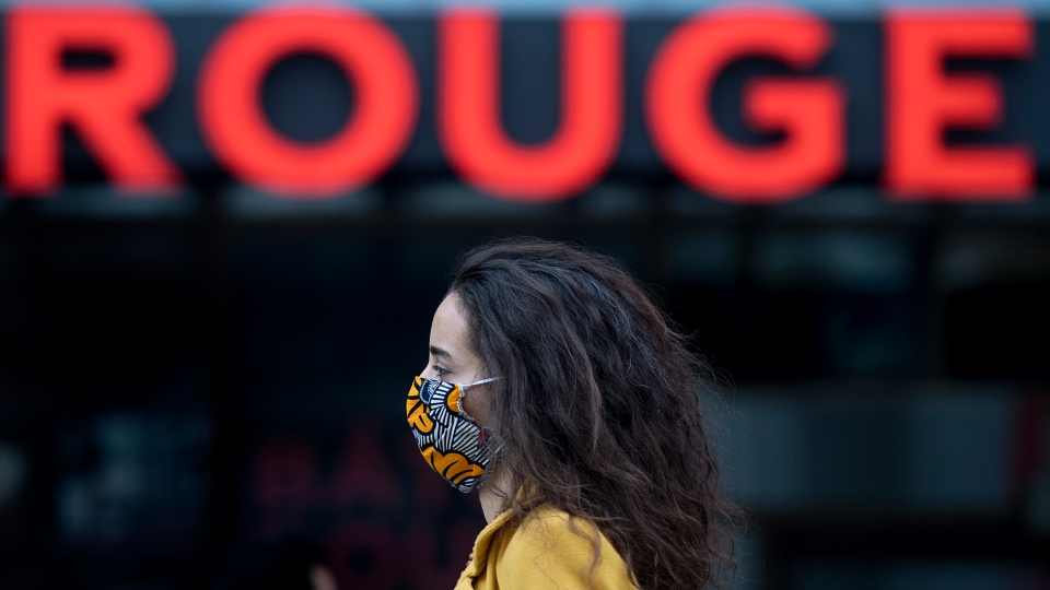 A woman wears a face mask as she walks by the word Rouge in Montreal, Saturday, Oct. 10, 2020, as the COVID-19 pandemic continues in Canada and around the world. Quebec continues to have over one thousand COVID-19 cases per day over the last week and has put much of the province in the red zone. THE CANADIAN PRESS/Graham Hughes