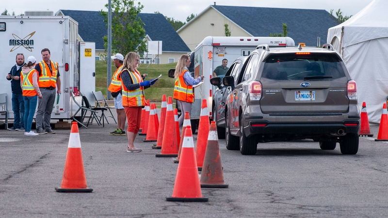 Volunteers examine the documents of motorists who just came off the Confederation Bridge in Borden-Carleton, P.E.I., Friday, July 3, 2020. THE CANADIAN PRESS/Brian McInnis