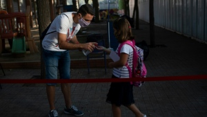 A girl has hand sanitizer sprayed into her hand in Spain. (AFP)