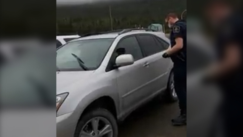 An officer from the Canada Border Services Agency begins a search of Thomas Winkler's car at the Fraser border crossing on Sept. 7. Winkler says one of the officers who searched his vehicle wore a mask while doing so, but the other did not. (Thomas Winkler)