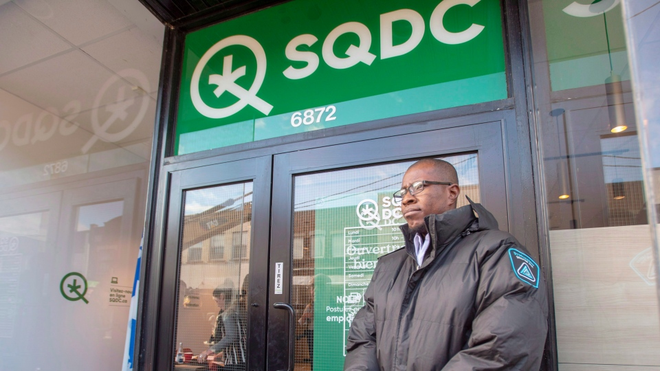 A security guard stands in front of a new Societe Quebecoise du Cannabis (SQDC) store before a media preview Tuesday, October 16, 2018 in Montreal. THE CANADIAN PRESS/Ryan Remiorz