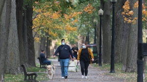 People wear face masks as they walk in a city park in Montreal, Saturday, Oct. 10, 2020, as the COVID-19 pandemic continues in Canada and around the world. THE CANADIAN PRESS/Graham Hughes