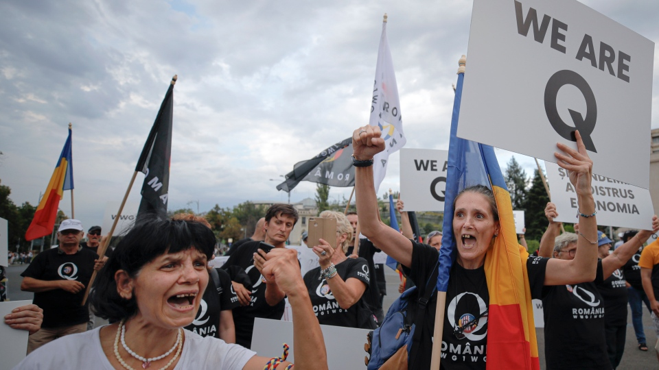 Romanian supporters of QAnon shout slogans against the government's measures to prevent the spread of COVID-19 infections, like wearing a face mask, during a rally in Bucharest, Romania, Monday, Aug. 10, 2020. QAnon is a U.S. conspiracy theory popular among some Trump supporters. (AP Photo/Vadim Ghirda)
