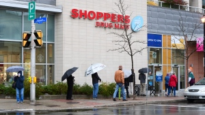 People line up to get an annual flu shot at a pharmacy in Ottawa on Thursday, Oct. 15, 2020. (Sean Kilpatrick/THE CANADIAN PRESS)