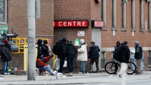 Men gather outside of a shelter in downtown Toronto on Saturday, March 28, 2020. THE CANADIAN PRESS/Colin Perkel