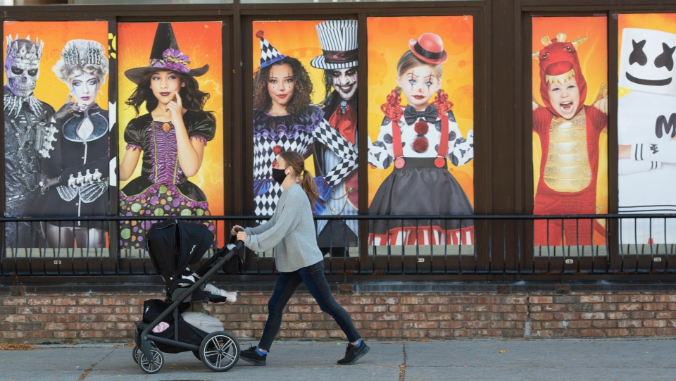 A woman walks past a Halloween shop in Montreal, Thursday, Oct. 15, 2020. The Quebec government announced that Halloween can go ahead with some restrictions amid the ongoing COVID-19 pandemic.THE CANADIAN PRESS/Ryan Remiorz