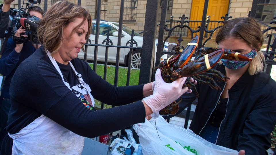Cheryl Maloney, a member of the Sipekne'katik First Nation, sells lobster outside the legislature in Halifax on Friday, Oct. 16, 2020. (THE CANADIAN PRESS /Andrew Vaughan)