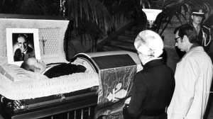 The body of Pierre Laporte, with Premier and Mrs. Robert Bourassa kneeling before it, lies in state Monday, Oct. 20, 1970 in the Montreal courthouse, attended by an honor guard of provincial police. A Quebec flag is draped over the coffin. Mr. Laporte, provincial labor minister, was kidnapped Oct. 10, 1999 by the FLQ and killed Saturday, Oct. 18 by political terrorists. (CP Wirephoto) 1999