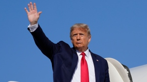 Then-U.S. President Donald Trump waves as he boards Air Force One, Saturday, Oct. 17, 2020, at Andrews Air Force Base, Md. Trump is en route to Michigan and Wisconsin. (AP Photo/Alex Brandon)