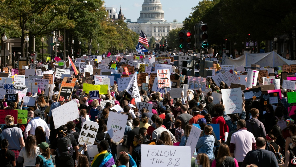 With the U.S Capitol in the back ground, demonstrators march on Pennsylvania Avenue during the Women's March in Washington, Saturday, Oct. 17, 2020. (AP Photo/Jose Luis Magana)
