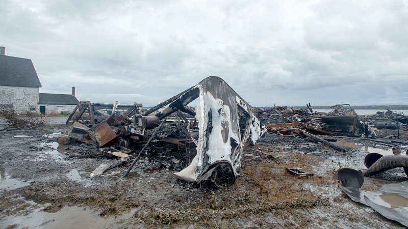 Debris from a burnt out fish plant is scattered along the shore in Middle West Pubnico, N.S. on Saturday, Oct. 17, 2020. A large fire destroyed a commercial building that was the scene of a confrontation earlier in the week between Indigenous and non-Indigenous fishermen. Tensions remain high over an Indigenous-led lobster fishery that has been the source of conflict. THE CANADIAN PRESS /Andrew Vaughan