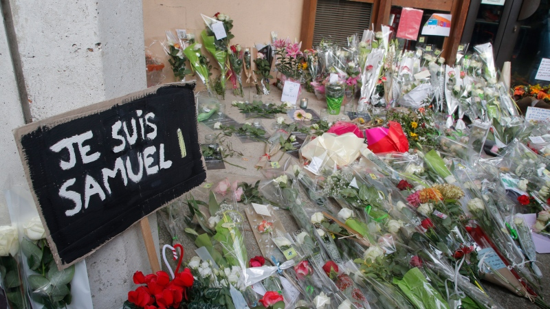 "A poster reading ""I am Samuel"" and flowers lay outside the school where slain history teacher Samuel Paty was working, Saturday, Oct. 17, 2020 in Conflans-Sainte-Honorine, northwest of Paris. French President Emmanuel Macron denounced what he called an ""Islamist terrorist attack"" against a history teacher decapitated in a Paris suburb Friday, urging the nation to stand united against extremism. The teacher had discussed caricatures of Islam's Prophet Muhammad with his class, authorities said. The suspected attacker was shot to death by police after Friday's beheading. (AP Photo/Michel Euler)"
