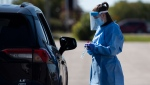 A paramedic prepares to administer a nasal swab at a drive through, pop-up COVID-19 test centre outside the Canadian Tire Centre, home of the NHL's Ottawa Senators, in Ottawa, Sunday, Sept. 20, 2020. THE CANADIAN PRESS/Justin Tang