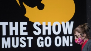 """A woman wears a face mask as she walks by a sign reading """"The Show Must Go On,"""" in Montreal, Saturday, October 17, 2020, as the COVID-19 pandemic continues in Canada and around the world. THE CANADIAN PRESS/Graham Hughes"""