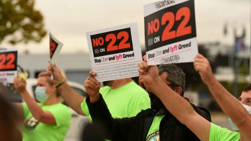 "Rideshare drivers hold signs supporting a ""No"" vote on Proposition 22 in Oakland, California on October 9, 2020. (AFP)"