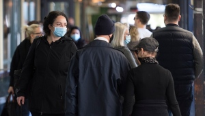 People wear face masks as they walk through a market in Montreal, Sunday, Oct. 18, 2020, as the COVID-19 pandemic continues in Canada and around the world. (THE CANADIAN PRESS/Graham Hughes)
