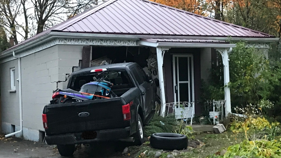 A pickup truck was left crashed into a home on Elliot Street on Monday, Oct. 19, 2020. (Sean Irvine / CTV London)