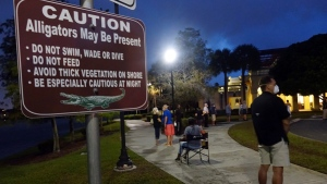 Voters wait in the dark before polls open on the first day of in-person early voting in Florida, at the Spanish River Library in Boca Raton, on Oct. 19, 2020. (Joe Cavaretta / South Florida Sun-Sentinel via AP)