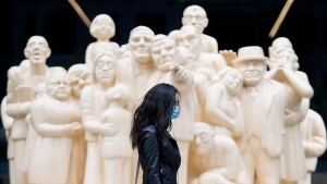 A woman wears a face mask as she walks by 'The Illuminated Crowd' on a street in Montreal, Sunday, Oct. 18, 2020, as the COVID-19 pandemic continues in Canada and around the world. THE CANADIAN PRESS/Graham Hughes