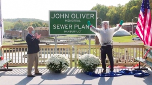 John Oliver, right, with Mayor Mark Boughton during a dedication ceremony for The John Oliver Memorial Sewer Plant, in Danbury, Conn. (HBO via AP)