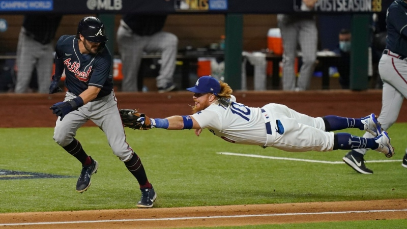 Los Angeles Dodgers third baseman Justin Turner tags Atlanta Braves' Dansby Swanson in a run down during the fourth inning in Game 7 of a baseball National League Championship Series, on Oct. 18, 2020. (Eric Gay / AP)