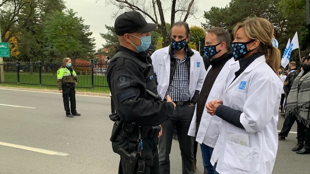 A police officer questions nurses protesting at the Jacques-Cartier Bridge on Oct. 19, 2020. (Photo/CTV News)