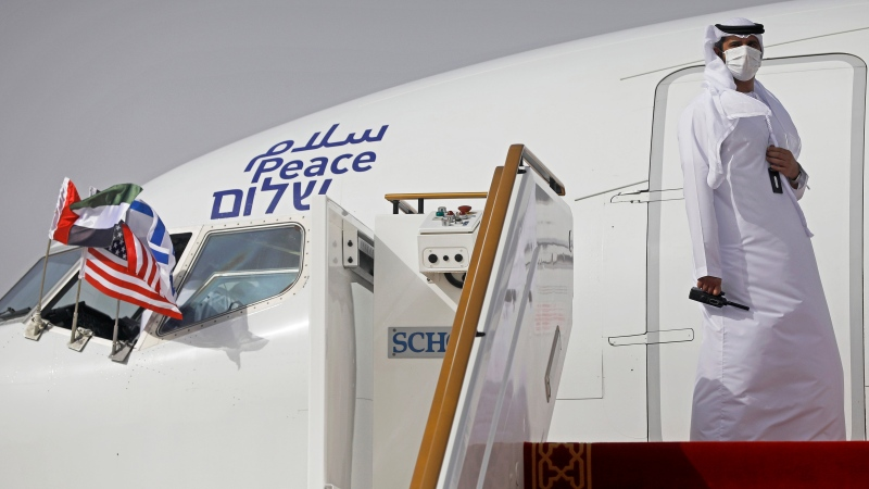 In this Monday, Aug. 31, 2020, file photo, an official stands at the door of an Israeli El Al airliner after it landed in Abu Dhabi, United Arab Emirates. The first commercial passenger flight to Israel by a carrier from the United Arab Emirates landed near Tel Aviv on Monday, Oct. 19, 2020, further cementing a normalization deal between the two countries. (Nir Elias/Pool Photo via AP, File)