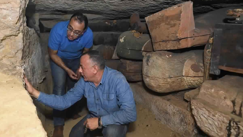 "This undated photo provided by the Egyptian Ministry of Tourism and Antiquities, Egyptian Prime Minister Mustafa Madbouly, left and Mostafa Waziri, Secretary General of the Supreme Council of Antiquities inspects a trove of ancient coffins and artifacts that Egyptian archaeologists recently unearthed in a vast necropolis south of Cairo, authorities announced Monday, Oct. 19, 2020, in Saqqara, south of Cairo, Egypt. The Tourism and Antiquities Ministry said in a statement that archaeologists found a ""large number"" of colorful, sealed sarcophagi buried more than 2,500 years ago. (Ministry of Tourism and Antiquities via AP)"
