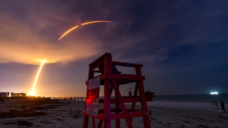 A SpaceX Falcon 9 lifts off rom Pad 39A at Kennedy Space Center early Friday, Aug. 7, 2020, as seen in this four-minute time exposure from Cocoa Beach, Fla. The rocket is carrying 57 Starlink satellites and two Earth observation spacecraft for BlackSky. (Malcolm Denemark/Florida Today via AP)