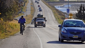 A biker leads a line of cars driving off the Homer Spit at about on Monday, Oct. 19, 2020, in Homer, Alaska after a tsunami evacuation order was issued for low-lying areas in Homer. (Michael Armstrong/Homer News via AP)