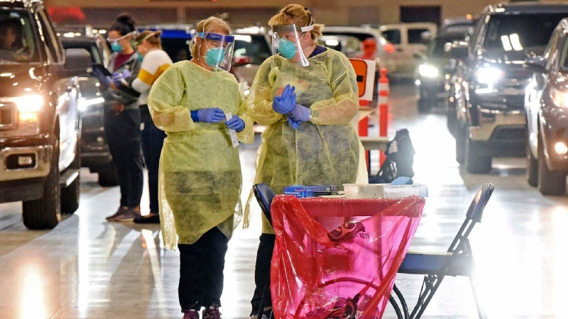 In this Sept. 8, 2020, file photo, Bismarck-Burleigh Public Health nurses Crys Kuntz, left, and Sara Nelson confer inside the Bismarck Event Center in Bismarck, N.D., where vehicles were lined up for the weekly drive-thru COVID-19 testing. A surge of coronavirus cases in Wisconsin and the Dakotas is forcing a scramble for hospital beds and raising political tensions, as the Upper Midwest and Plains emerge as one of the nation's most troubling hotspots. (Tom Stromme/The Bismarck Tribune via AP, File)