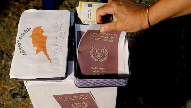 A demonstrator takes a mock copy of Cyprus passport during a demonstration against corruption in Nicosia, Cyprus, on Oct. 14, 2020. (Petros Karadjias / AP)