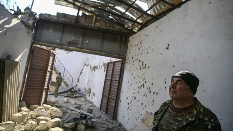 The mayor of Martakert Misha Gyurjian stands inside a building destroyed by shelling. (AFP)