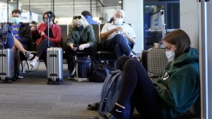 FILE- In this Oct. 15, 2020, file photo, passenger Cari Driggs, right, from Provo, Utah, waits to board a United Airlines flight to Hawaii for vacation at San Francisco International Airport in San Francisco. The CDC is strongly recommending that passengers on planes, trains and buses wear masks, but it's still stopping short of requiring face coverings to prevent spreading COVID-19. All leading U.S. airlines require passengers other than small children to wear masks during flights, but enforcement can be spotty. The Federal Aviation Administration has declined to require masks. (AP Photo/Jeff Chiu, File)