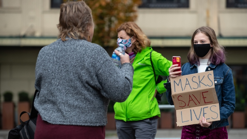 "A young woman holding a sign that says ""Masks Save Lives"" is approached by a woman attending a rally and march being held by protesters opposed to COVID-19 regulations, in Vancouver, on Sunday, October 18, 2020. THE CANADIAN PRESS/Darryl Dyck"