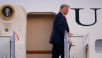 In this file photo, U.S. President Donald Trump stands at the top of the steps of Air Force One at Andrews Air Force Base, Md., Tuesday, Oct. 20, 2020. Trump is heading to Erie, Pa., for a campaign rally. (AP Photo/Susan Walsh)