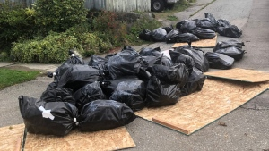"Dozens of bags labelled ""Caution: Asbestos"" are seen in a back alley in East Vancouver on Tuesday, Oct. 20, 2020."