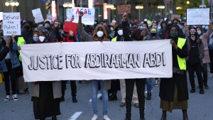 People stand on Elgin Street during a rally after an Ottawa Police constable was found not guilty of manslaughter, aggravated assault and assault with a weapon in connection with the 2016 death of Abdirahman Abdi, a 37-year old Black man, in Ottawa, on Tuesday, Oct. 20, 2020. THE CANADIAN PRESS/Justin Tang