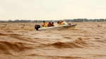 Rescue workers travel by boat on a swelling river to access a flooded area in Quang Binh province, Vietnam, Monday, Oct. 12, 2020. (Nguyen Van Ty/VNA via AP)