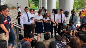 University students read a statement about a motion they lodged with the court outside Bangkok Civil Court in Bangkok, Thailand, Wednesday, Oct. 21, 2020. (AP Photo/Jerry Harmer)