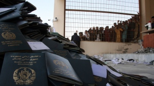 Afghans wait to collect their passports with Pakistani visas inthe city of Jalalabad east of Kabul, Afghanistan, Wednesday, Oct. 21, 2020. (AP Photo/Wali Sabawoon)