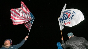 Steven Lantz-Gordon, 24, at left, of Harborcreek Township, waves a flag in support of President Donald Trump near David Oberg, 60, at right, of Grand Valley, who raises a flag in support of Democratic presidential candidate and former Vice President Joe Biden in Millcreek Township, Pa., on  Oct. 20, 2020. (Christopher Millette / Erie Times-News via AP)