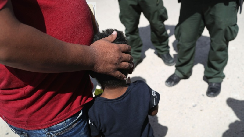 U.S. Border Patrol agents take a father and son from Honduras into custody near the U.S. (Credit: John Moore / Getty Images via CNN)