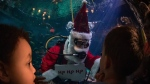 An interpreter dressed as Scuba Claus interacts with children at the Vancouver Aquarium, on Dec. 23, 2019. (Darryl Dyck / THE CANADIAN PRESS)