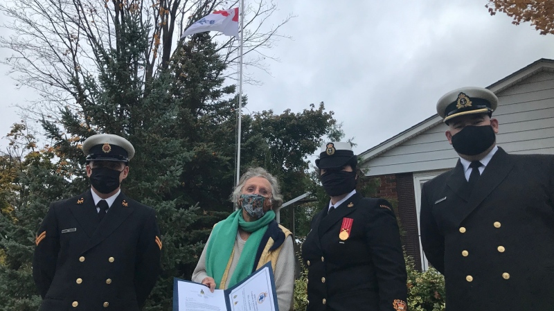 Members of HMCS Prevost, the London naval reserve station, stand with Lucienne de Vries, the 'Flag Lady' of Sarnia, Ontario on Wednesday, Oct. 21, 2020. (Sean Irvine / CTV News)