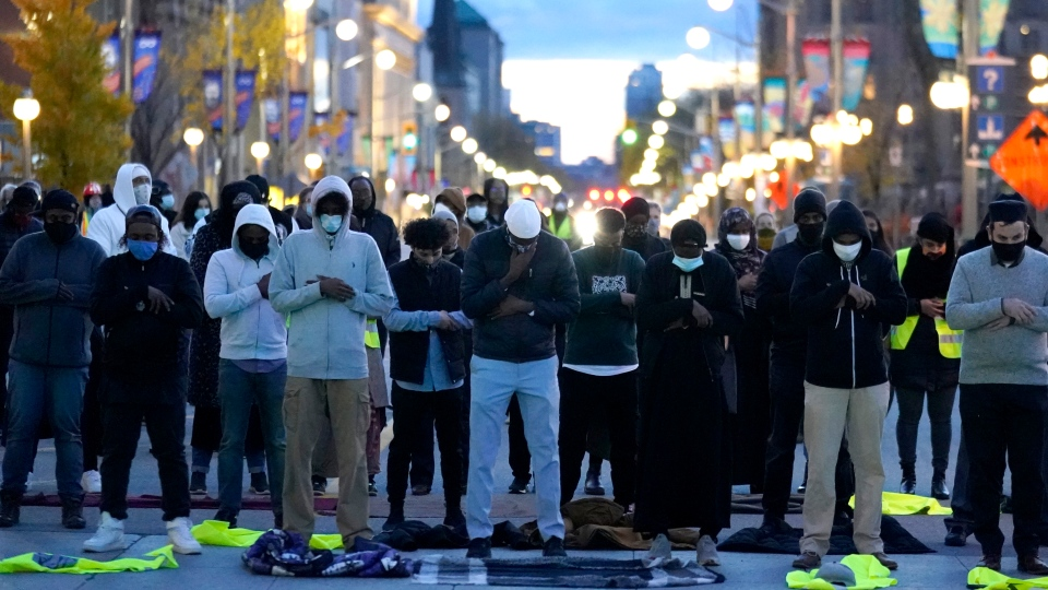 Community members pray in memory of Abdirahman Abdi as the rally blocks the intersection in front of Parliament Hill, after an Ottawa Police constable was found not guilty of manslaughter, aggravated assault and assault with a weapon in connection with the 2016 death of Abdi, a 37-year old Black man, in Ottawa, on Tuesday, Oct. 20, 2020. (Justin Tang/THE CANADIAN PRESS)