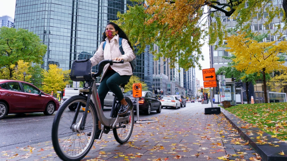 A woman rides her bike in downtown Montreal, on Tuesday, October 20, 2020. THE CANADIAN PRESS/Paul Chiasson