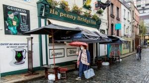 A woman walks down a street wearing a mask in Ireland. (AFP)