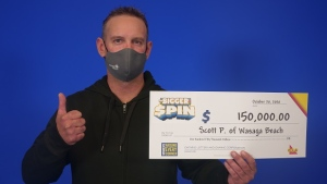 Scott Paterson, 40, of Wasaga Beach holds his big cheque at the OLG Prize Centre in Toronto, Ontario. (OLG)
