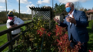 NDP Leader John Horgan speaks to a passerby following a round table meeting in the backyard of a home in Langley, B.C., on Wednesday, October 21, 2020. THE CANADIAN PRESS/Jonathan Hayward